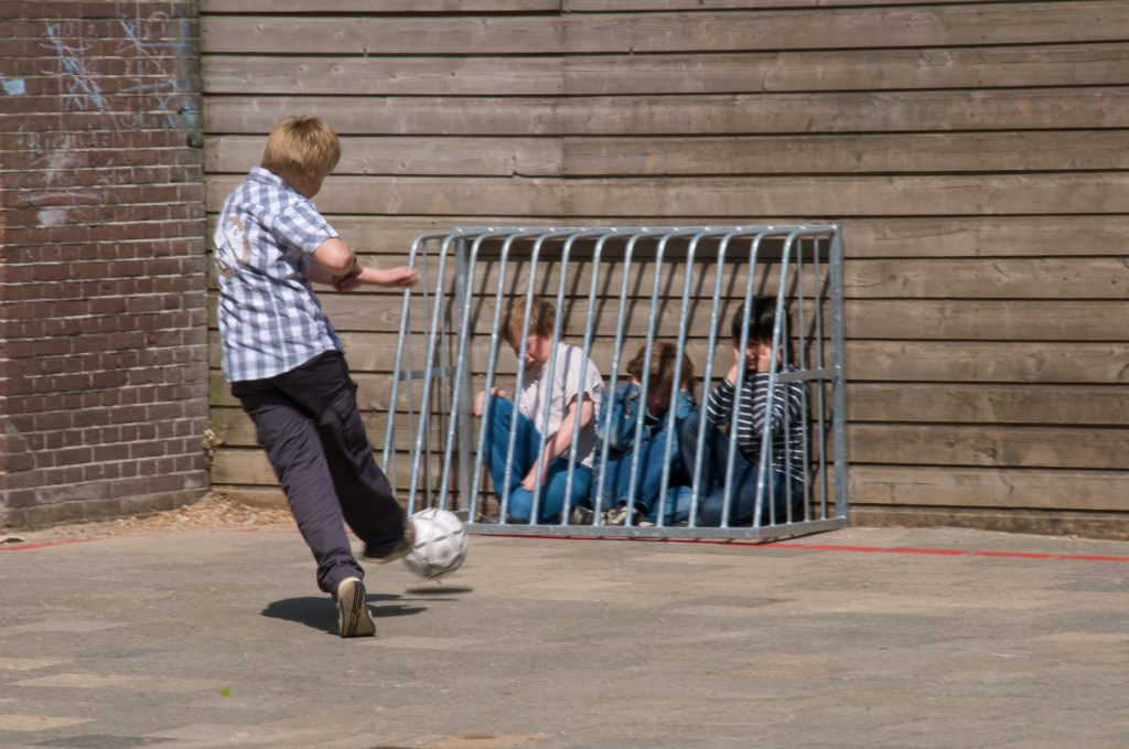 A boy kicking a soccer ball at a cage holding several smaller boys