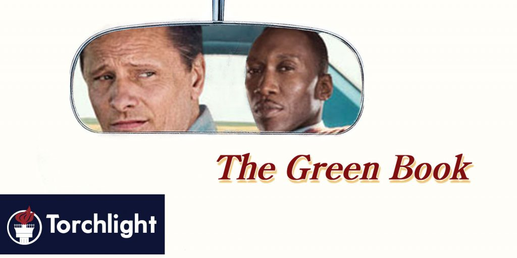 The lead characters of the Green Book looking back from a rearview mirror