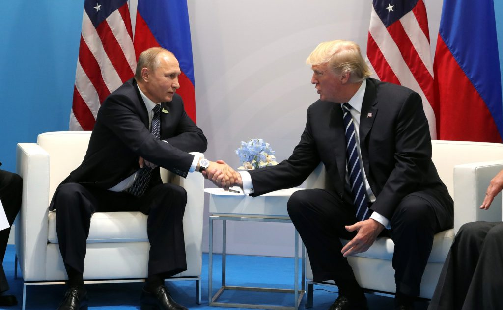 Vladimir Putin (left) and Donald Trump shaking hands at the 2017 G-20 Hamburg Summit
